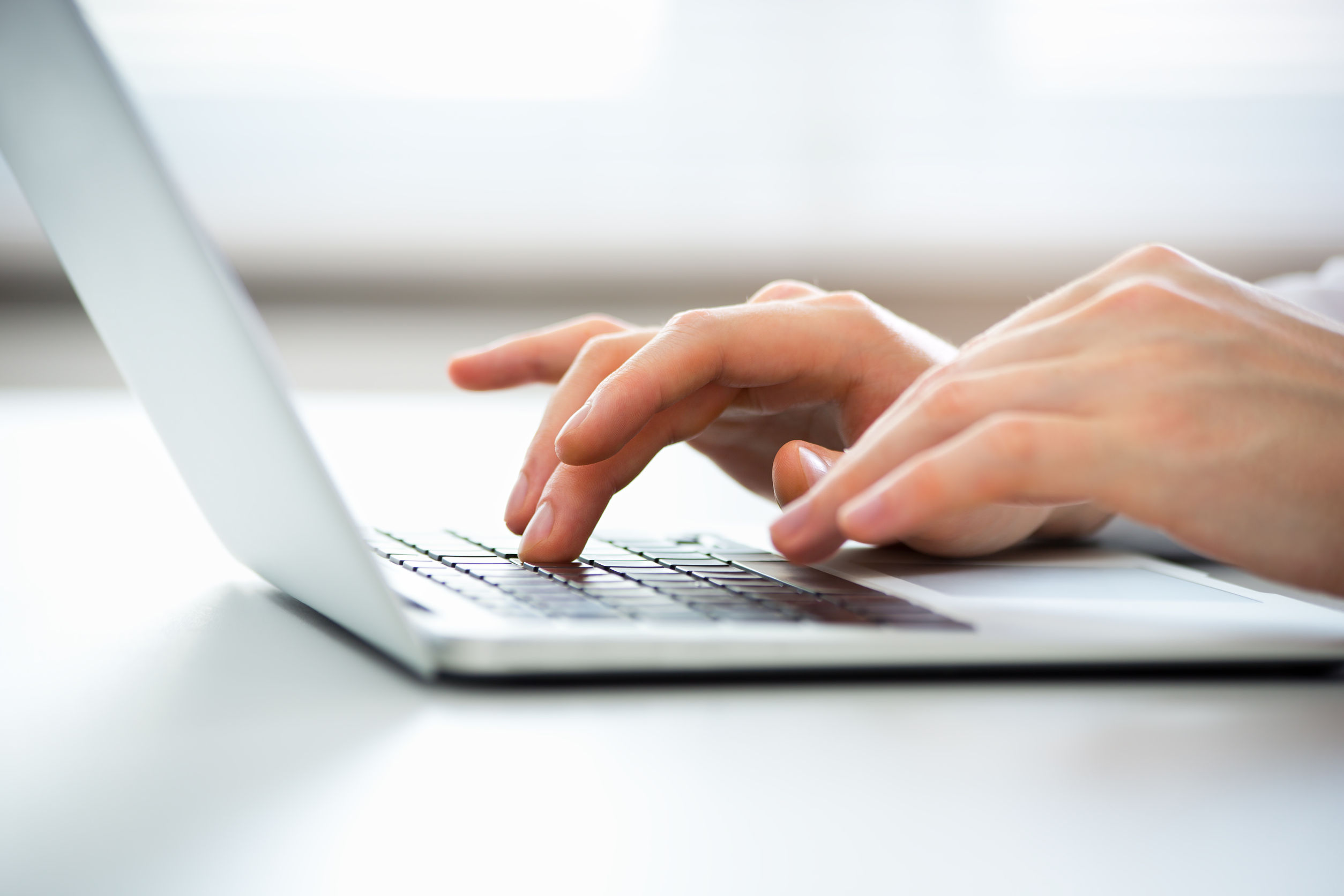 65142940 - close-up of hands of business man typing on a laptop.